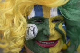 A Brazil soccer fan in costume waits for the start of a live broadcast of a 2018 Russia World Cup soccer match between Brazil and Mexico in Rio de Janeiro, Brazil, Monday, July 2, 2018. (AP Photo/Leo Correa)