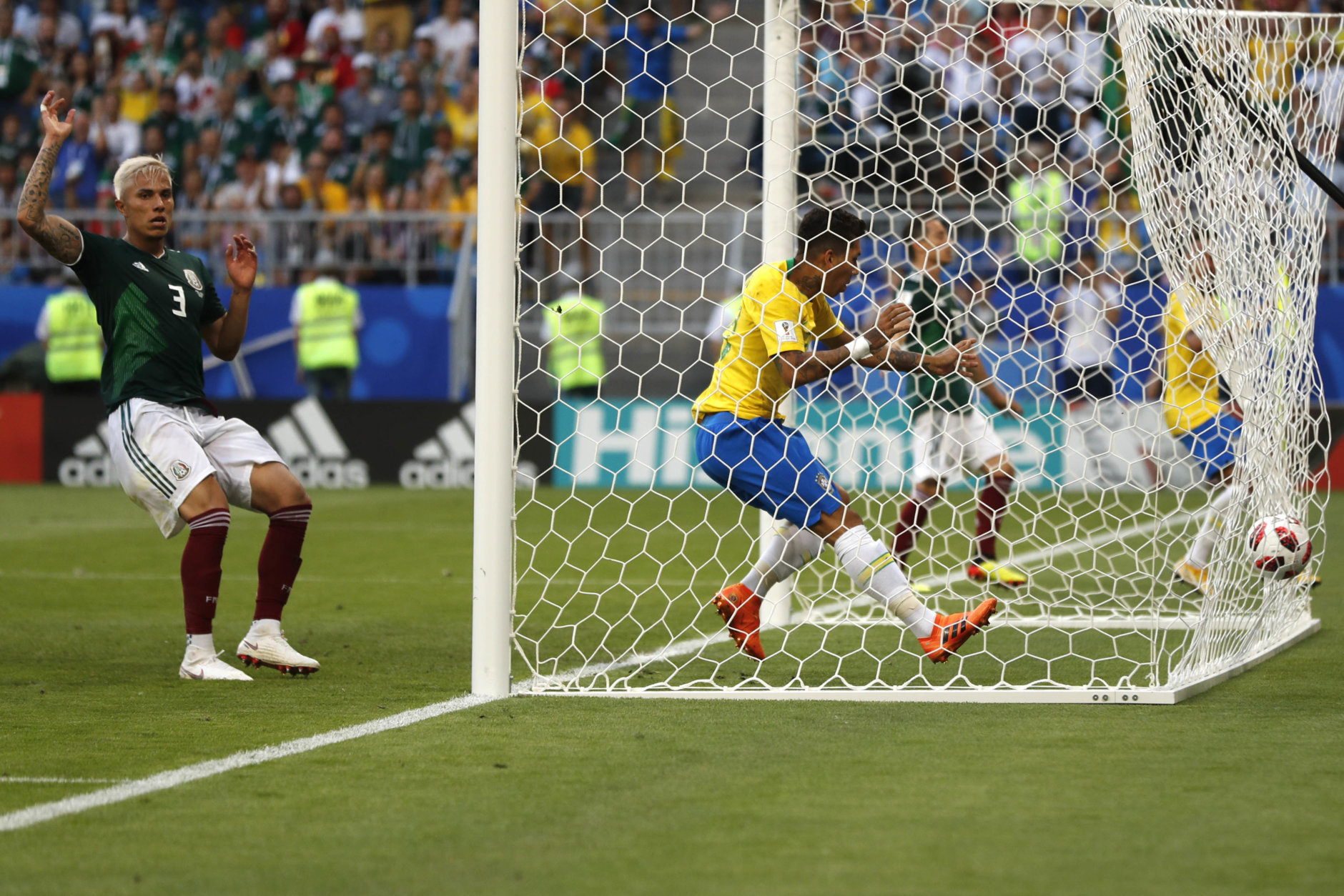 Brazil's Roberto Firmino scores his side's second goal during the round of 16 match between Brazil and Mexico at the 2018 soccer World Cup in the Samara Arena, in Samara, Russia, Monday, July 2, 2018. (AP Photo/Frank Augstein)