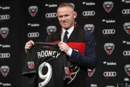 English soccer star Wayne Rooney, the all-time leading scorer for England's national team and Manchester United in the Premier League, poses with his new jersey during a news conference announcing his signing with MLS team D.C. United, Monday, July 2, 2018, at the Newseum in Washington. (AP Photo/Jacquelyn Martin)