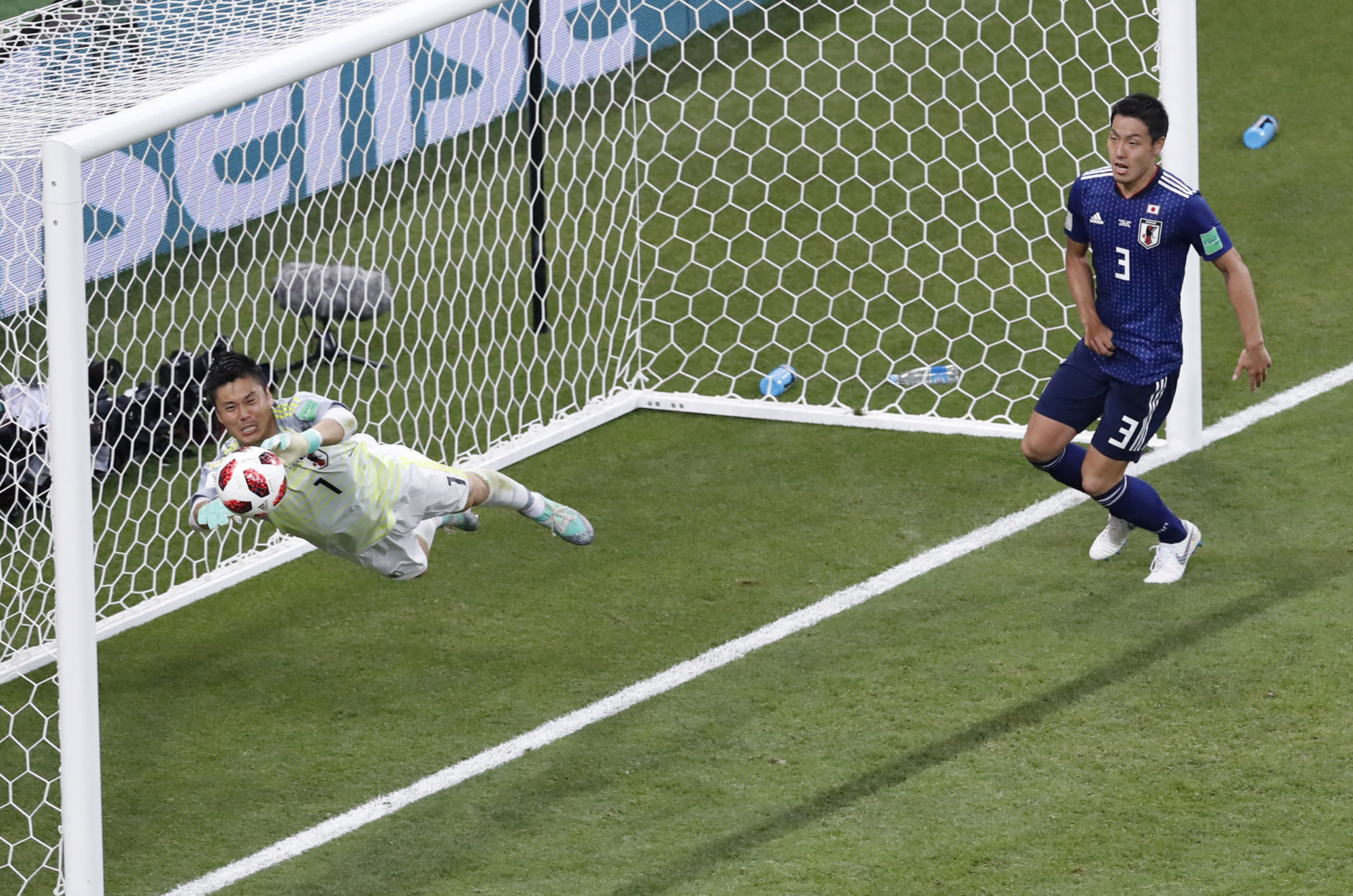 Japan goalkeeper Eiji Kawashima, left, saves a ball during the round of 16 match between Belgium and Japan at the 2018 soccer World Cup in the Rostov Arena, in Rostov-on-Don, Russia, Monday, July 2, 2018. (AP Photo/Hassan Ammar)