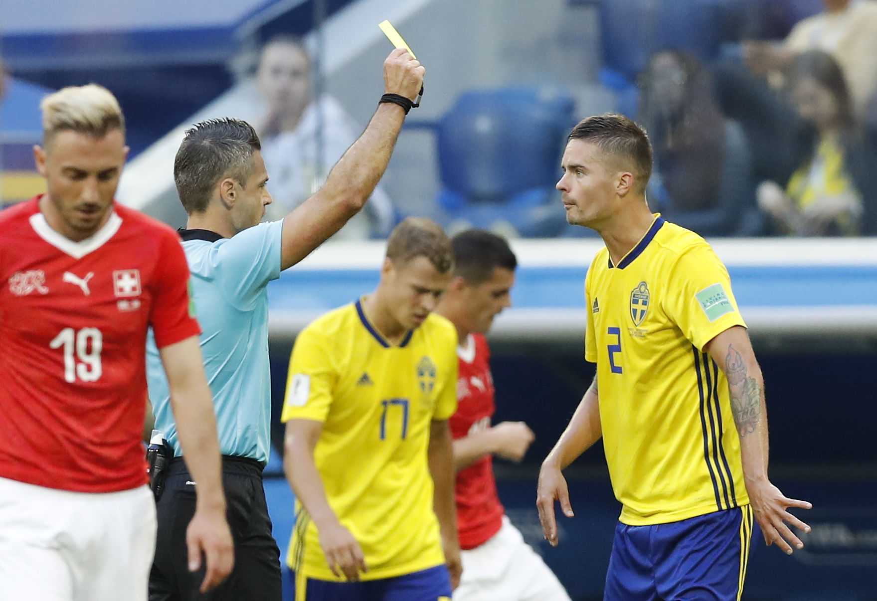 Referee Damir Skomina from Slovenia, second left, shows a yellow card to Sweden's Mikael Lustig during the round of 16 match between Switzerland and Sweden at the 2018 soccer World Cup in the St. Petersburg Stadium, in St. Petersburg, Russia, Tuesday, July 3, 2018. (AP Photo/Efrem Lukatsky)