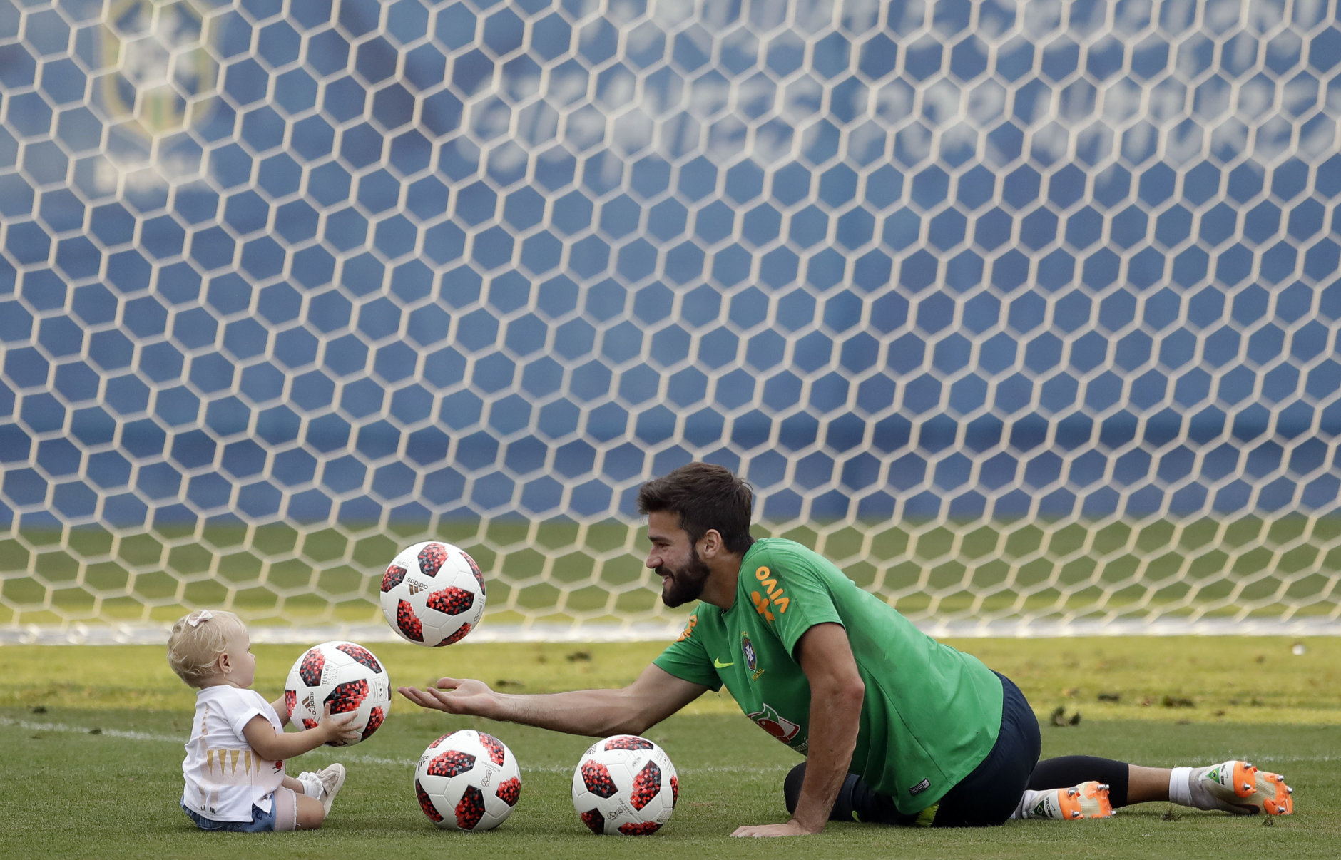 Brazil goalkeeper Alisson plays with his daughter Helena during a training session, in Sochi, Russia, Tuesday, July 3, 2018. Brazil will face Belgium on July 6 in the quarterfinals for the soccer World Cup. (AP Photo/Andre Penner)