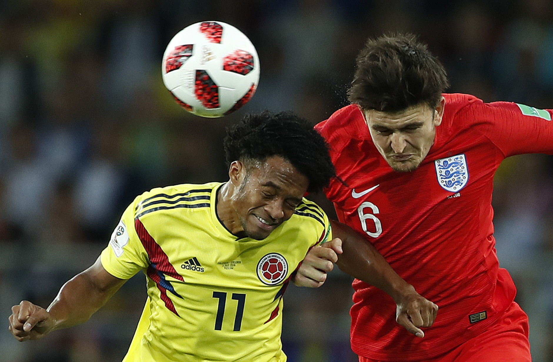 Colombia's Juan Cuadrado, left, and England's Harry Maguire challenge for the ball during the round of 16 match between Colombia and England at the 2018 soccer World Cup in the Spartak Stadium, in Moscow, Russia, Tuesday, July 3, 2018. (AP Photo/Alastair Grant)