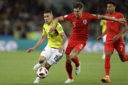 Colombia's Mateus Uribe, left, and England's John Stones fight for the ball during the round of 16 match between Colombia and England at the 2018 soccer World Cup in the Spartak Stadium, in Moscow, Russia, Tuesday, July 3, 2018. (AP Photo/Matthias Schrader)