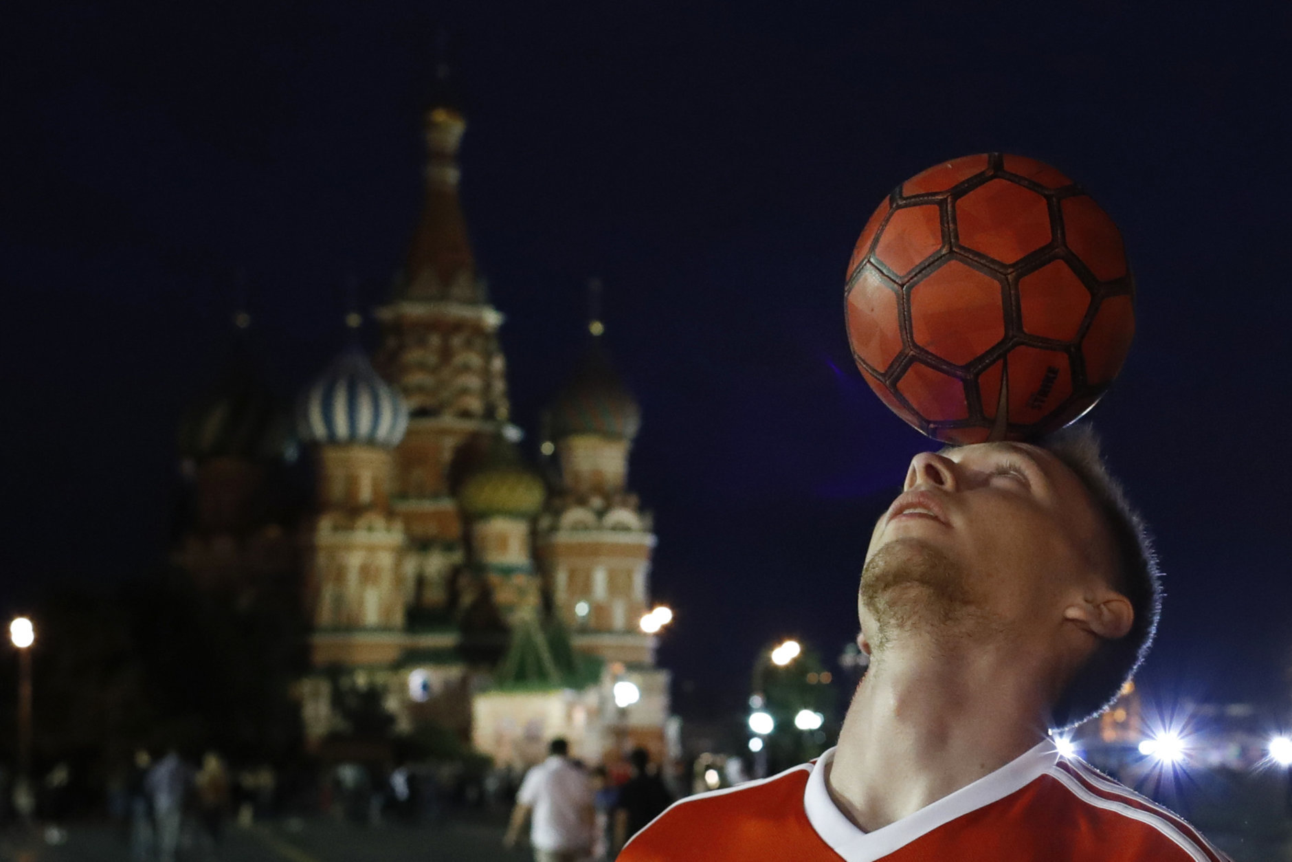A Russian soccer fan shows off his ball skills as he plays with tourists and soccer fans in Red Square during the 2018 soccer World Cup in Moscow, Russia, Tuesday, July 3, 2018. (AP Photo/Hassan Ammar)