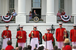 President Donald Trump, top center, accompanied by first lady Melania Trump, places his hand over his heart during the playing of the national anthem during an afternoon picnic for military families on the South Lawn of the White House, Wednesday, July 4, 2018, in Washington. (AP Photo/Alex Brandon)