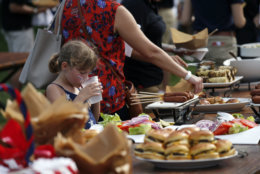 A child takes a drink in front of the food buffet during an afternoon picnic for military families on the South Lawn of the White House, Wednesday, July 4, 2018, in Washington. (AP Photo/Alex Brandon)