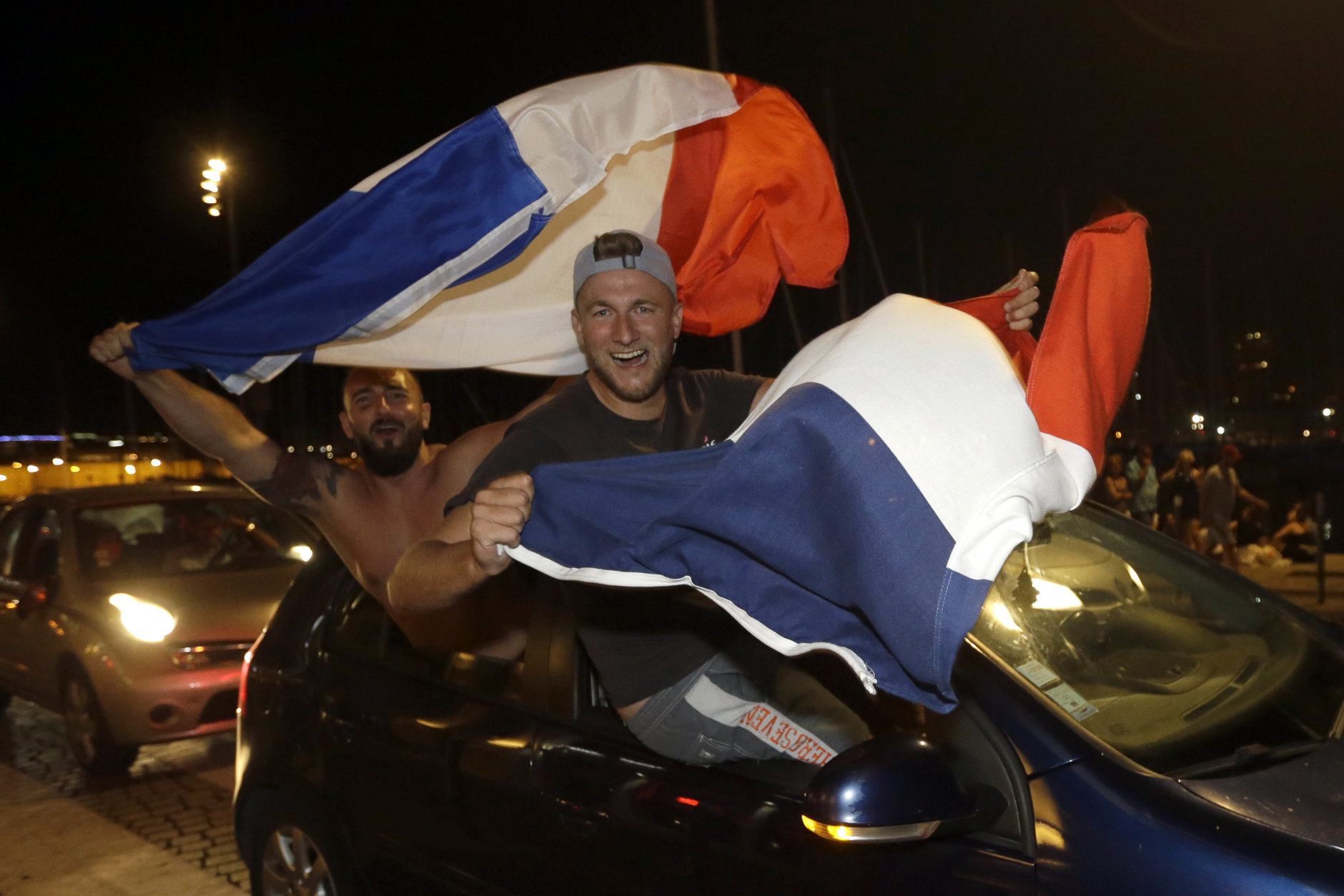 French soccer fans wave national flags while celebrating their team victory after watching the semifinal match between France and Belgium at the 2018 soccer World Cup, in Marseille, southern France, Tuesday July 10, 2018. France has advanced to the World Cup final for the first time since 2006 with a 1-0 win over Belgium. (AP Photo/Claude Paris)