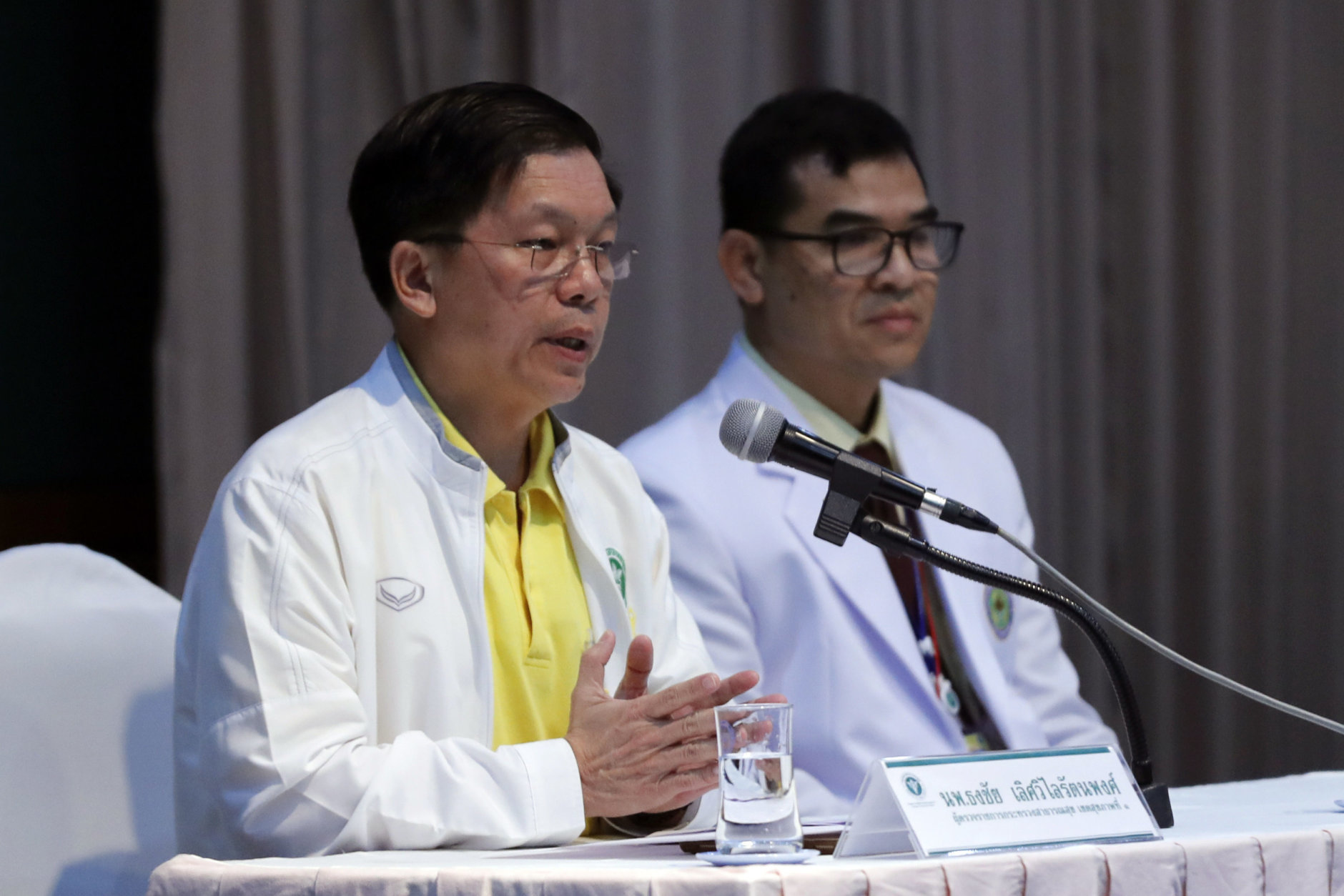Thongchai Lertwilairatanapong, a public health inspector, left, speaks during a press conference at a hospital in Chiang Rai province, northern Thailand, Wednesday, July 11, 2018. Thongchai said the soccer teammates rescued from a flooded cave lost weight during their two-week ordeal but had water while they were trapped and are in good health. (AP Photo/Vincent Thian)