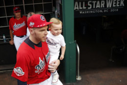 National League, Atlanta Braves Freddie Freeman holds his 22-month old child Charlie in the dugout during batting practice before the MLB Baseball Home Run Derby, at Nationals Park, Monday, July 16, 2018, in Washington. (AP Photo/Alex Brandon)