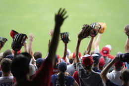 Fans vies for a thrown baseball ahead of the All-Star Home Run Derby Baseball event, Monday, July 16, 2018, at Nationals Park, Washington. The 89th MLB baseball All-Star Game will be played Tuesday. (AP Photo/Carolyn Kaster)