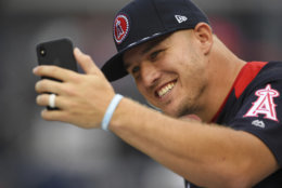 American League, Los Angeles Angels outfielder Mike Trout takes a photo on the field ahead of the All-Star Home Run Derby Baseball event, Monday, July 16, 2018, at Nationals Park, in Washington. The 89th MLB baseball All-Star Game will be played Tuesday. (AP Photo/Patrick Semansky)