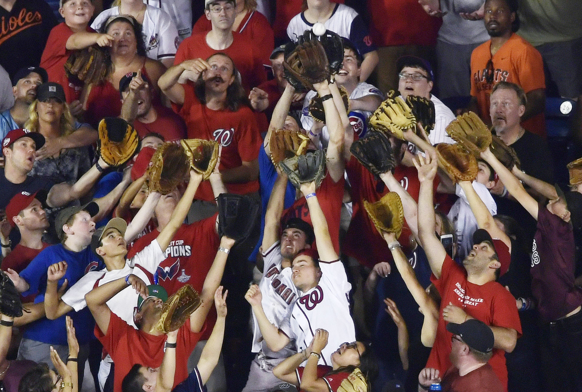 Fans reach for a home run ball during the MLB Home Run Derby, at Nationals Park, Monday, July 16, 2018 in Washington. The 89th MLB baseball All-Star Game will be played Tuesday. (AP Photo/Susan Walsh)