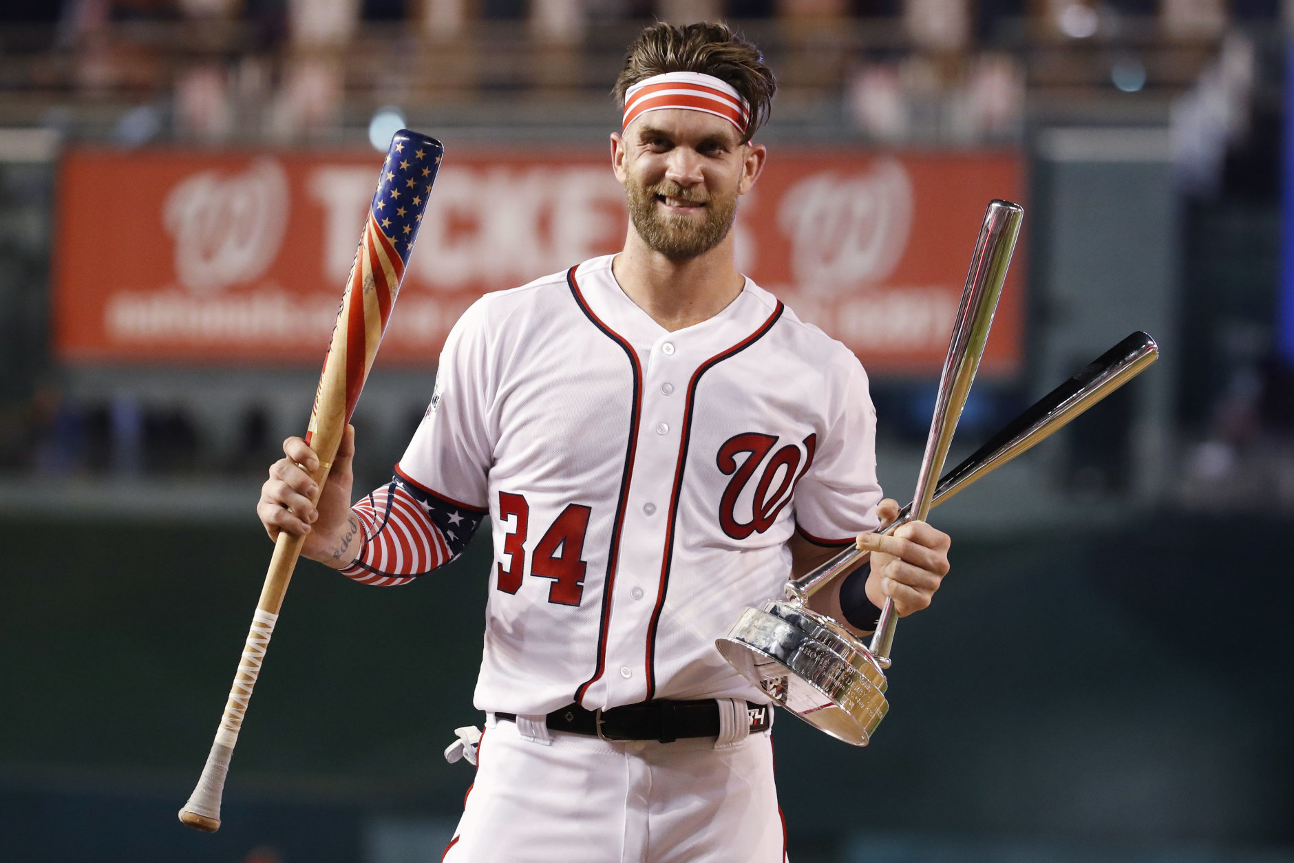 Washington Nationals Bryce Harper (34) holds his bat and the trophy after winning the Major League Baseball Home Run Derby Monday, July 16, 2018 in Washington. (AP Photo/Alex Brandon)