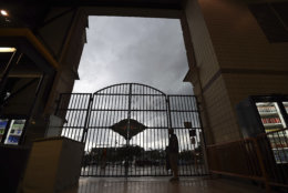 A fan stays dry as thunderstorms pass over Oriole Park at Camden Yards before a baseball game between the Baltimore Orioles and the Tampa Bay Rays on Friday, July 27, 2018, in Baltimore. (AP Photo/Gail Burton)