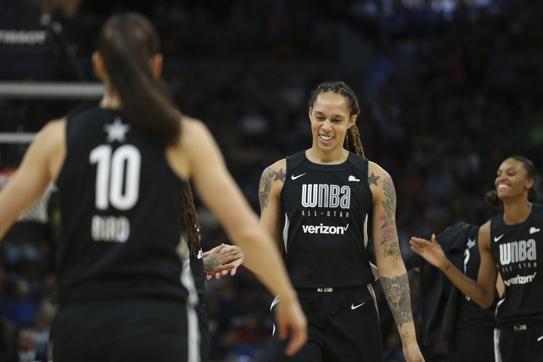 Team Delle Donne's Brittney Griner, middle, smiles as she high-fives teammate Seimone Augustus in the first half of the WNBA All-Star basketball game against Team Candace Parker, Saturday, July 28, 2018 in Minneapolis. (AP Photo/Stacy Bengs)