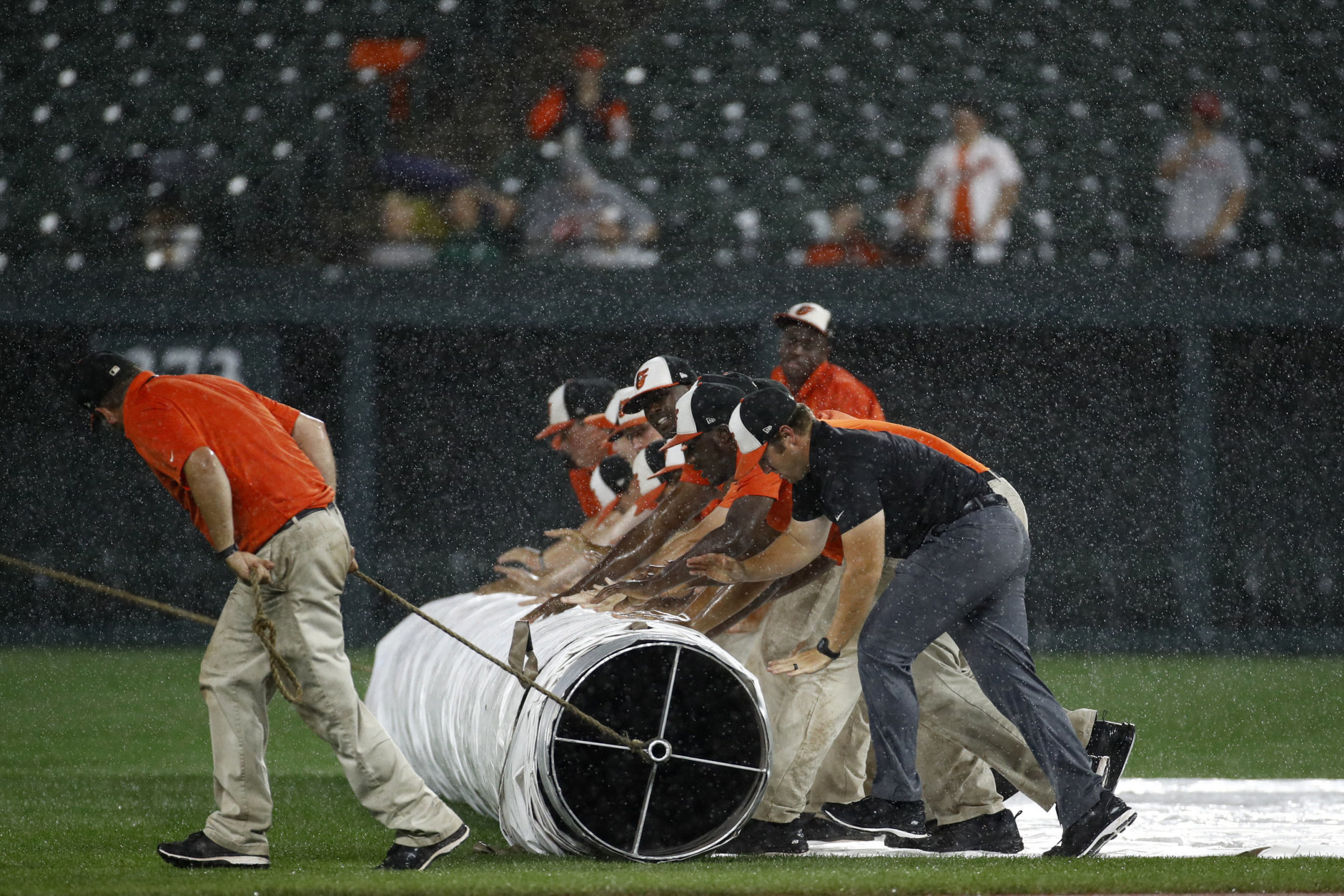 Grounds crew members roll a tarp over the field during a rain delay in a baseball game between the Boston Red Sox and the Baltimore Orioles, Tuesday, July 24, 2018, in Baltimore. (AP Photo/Patrick Semansky)