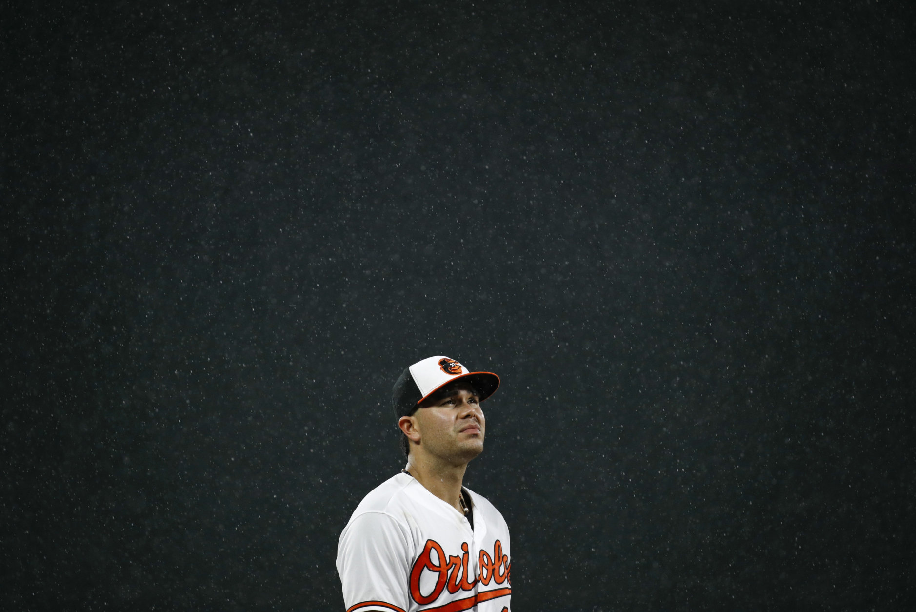 Baltimore Orioles third baseman Renato Nunez looks up as rain falls in the sixth inning of a baseball game against the Boston Red Sox, Tuesday, July 24, 2018, in Baltimore. (AP Photo/Patrick Semansky)