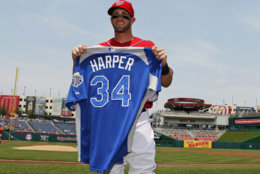 Washington Nationals right fielder Bryce Harper (34) holds his All Star jersey during a ceremony before a baseball with the Colorado Rockies game Sunday, July 8, 2012 in Washington. Harper was named to the All Star game yesterday. (AP Photo/Alex Brandon)