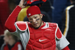 St. Louis Cardinals catcher Yadier Molina puts on his mask after chasing a foul ball during a baseball game against the Pittsburgh Pirates in Pittsburgh, Saturday, April 28, 2018. (AP Photo/Gene J. Puskar)
