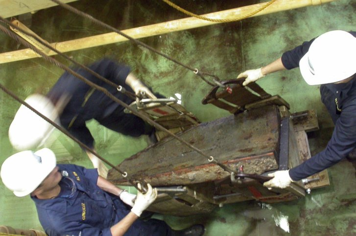 friends of the hunley inc shows workers lifting a keel block from the hunley submarine out of a 75000 gallon conservation tank at the warren lasch