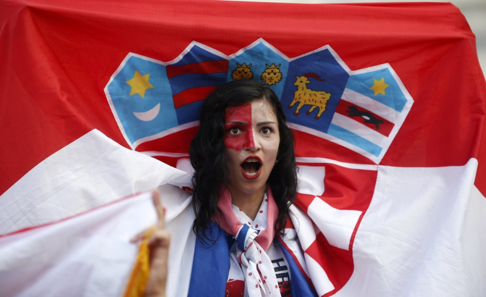 A Croatian soccer fan cheers as they watch a television broadcast of the Russia 2018 World Cup match between France and Croatia in downtown Zagreb, Croatia, Sunday, July 15, 2018. (AP Photo/Darko Vojinovic)