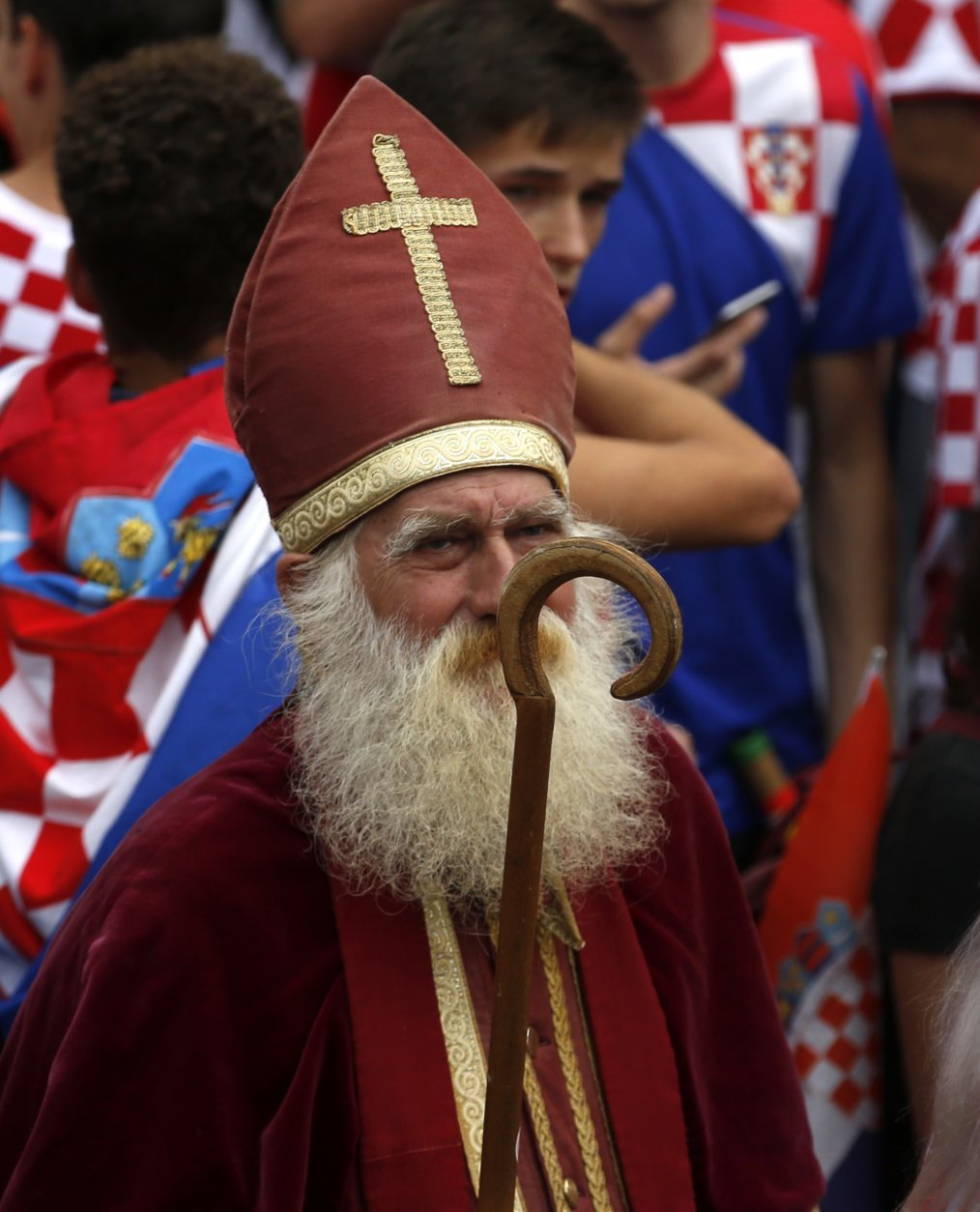 A priest is seen in the crowds during a television broadcast of the Russia 2018 World Cup match between France and Croatia in downtown Zagreb, Croatia, Sunday, July 15, 2018. (AP Photo/Darko Vojinovic)