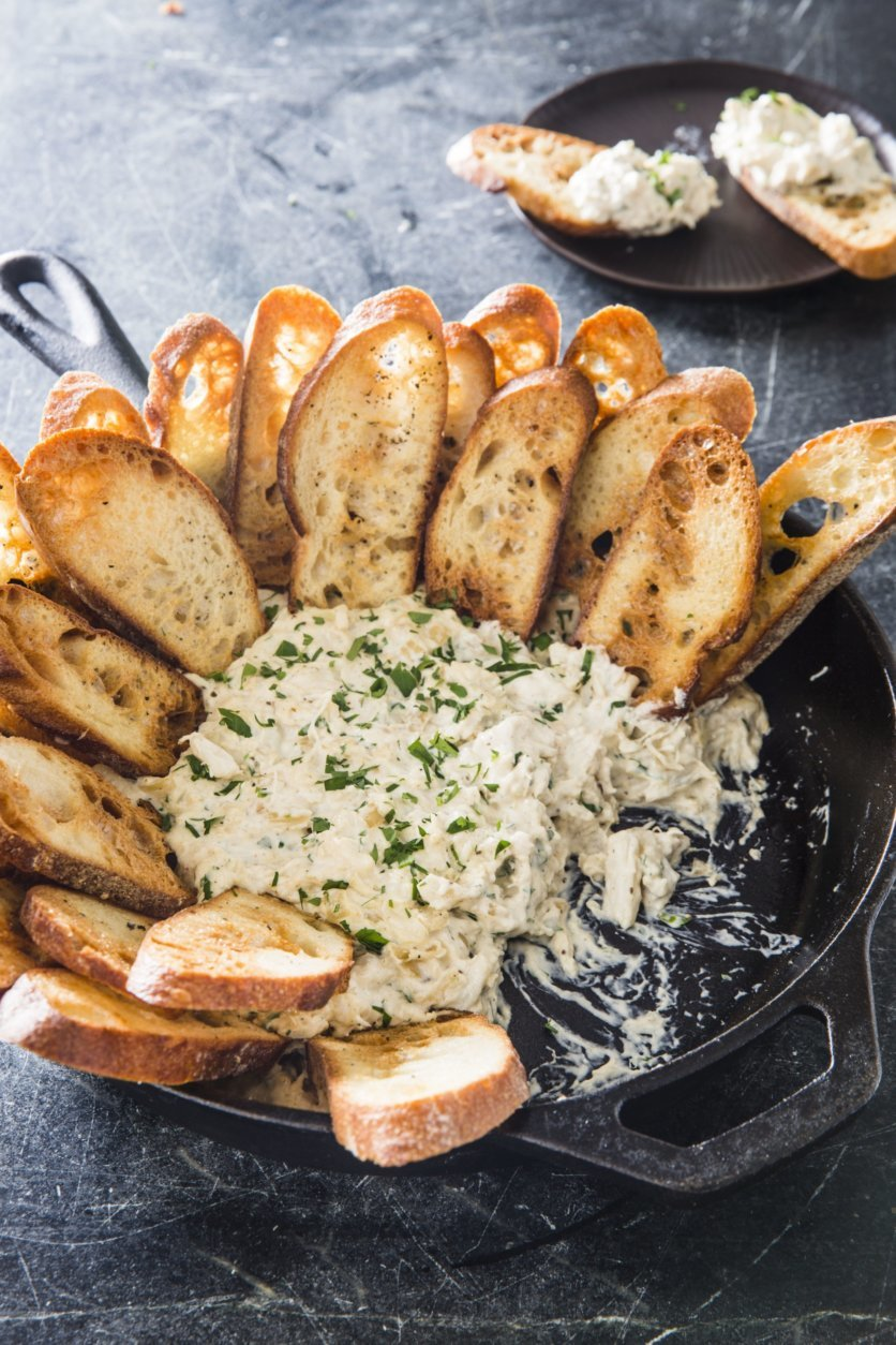 """This undated photo provided by America's Test Kitchen in July 2018 shows baked crab dip with crostini in Brookline, Mass. This recipe appears in the cookbook """"Cook's Illustrated All-Time Best Appetizers."""" (Joe Keller/America's Test Kitchen via AP)"""