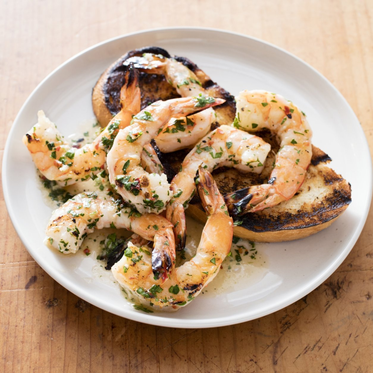 """This undated photo provided by America's Test Kitchen in July 2018 shows grilled shrimp with spicy lemon-garlic sauce in Brookline, Mass. This recipe appears in the cookbook """"Master Of The Grill."""" (Daniel J. van Ackere/America's Test Kitchen via AP)"""
