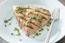 """This undated photo provided by America's Test Kitchen in July 2018 shows grilled tuna steaks with lime-ginger vinaigrette in Brookline, Mass. This recipe appears in """"The Complete Make-Ahead Cookbook."""" (Carl Tremblay/America's Test Kitchen via AP)"""