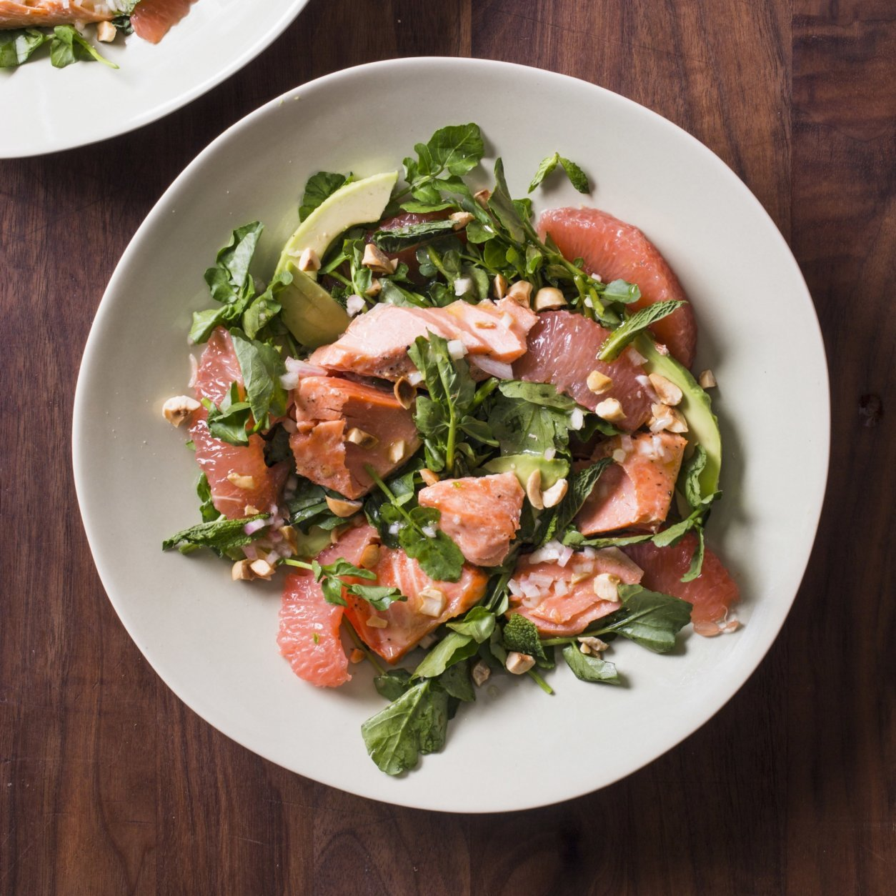 """This undated photo provided by America's Test Kitchen in July 2018 shows a salmon, avocado, grapefruit and watercress salad in Brookline, Mass. This recipe appears in the cookbook """"Dinner Illustrated."""" (Carl Tremblay/America's Test Kitchen via AP)"""