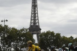 Tour de France winner Britain's Geraint Thomas, wearing the overall leader's yellow jersey, rides in front of the Eiffel Tower during the twenty-first stage of the Tour de France cycling race over 116 kilometers (72.1 miles) with start in Houilles and finish on Champs-Elysees avenue in Paris, France, Sunday July 29, 2018. (AP Photo/Francois Mori)