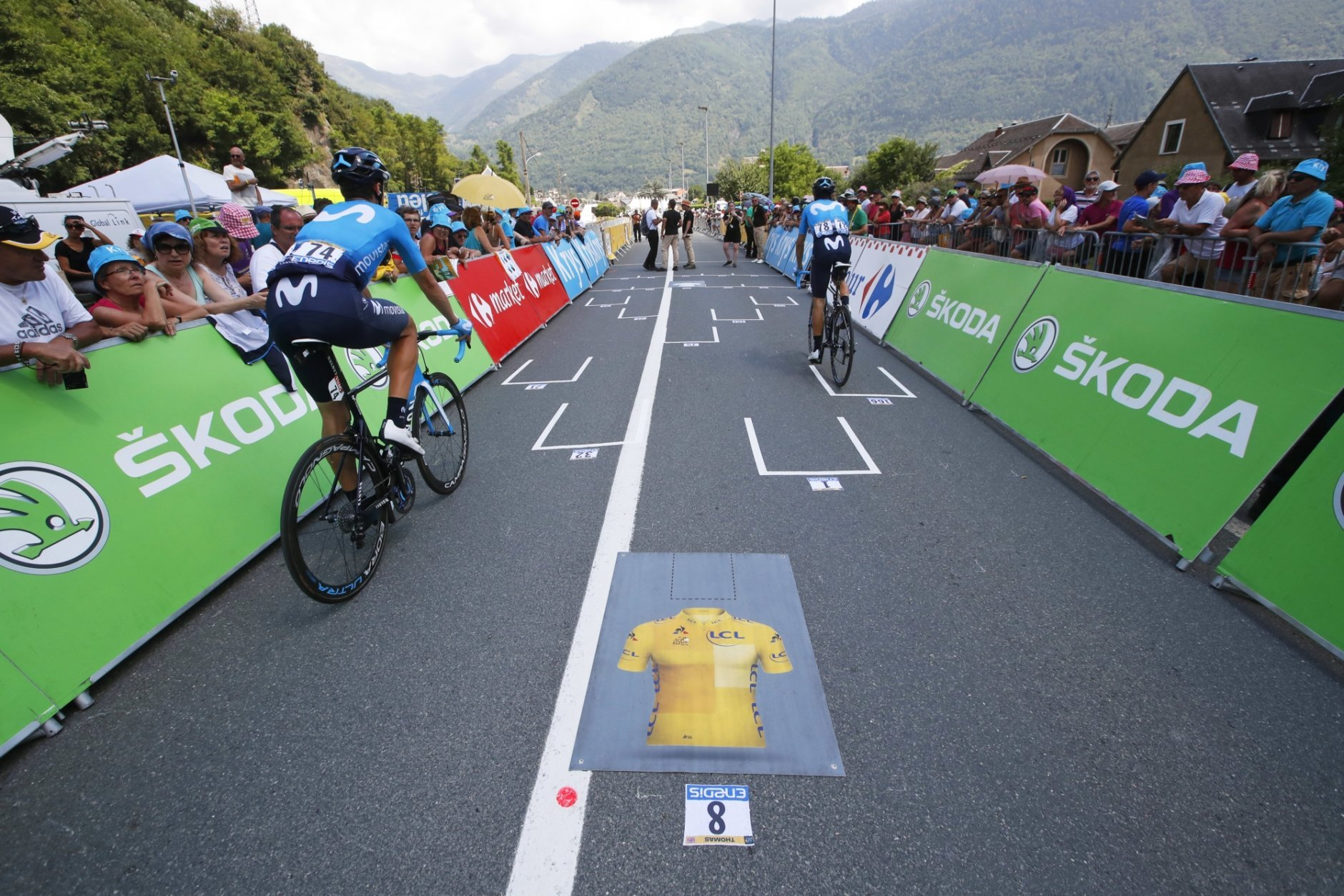 Spain's Imanol Erviti, left, and Spain's Alejandro Valverde, right, pass the Formula One-like start grid with overall leader Britain's Geraint Thomas's spot marked by the overall leader's yellow jersey, prior to the seventeenth stage of the Tour de France cycling race over 65 kilometers (40.4 miles) with start in Bagneres-de-Luchon and finish in Saint-Lary-Soulan, Col du Portet pass, France, Wednesday July 25, 2018. The Tour de France thinks it has some solutions to liven up the action with today's shorter mountain stage with three grueling climbs, including an uphill finish, intermediate bonus sprints, and a Formula One-like grid start. (AP Photo/Christophe Ena)