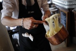 """In this photo taken on Tuesday, June 12, 2018, Waiter Michael prepares to serve the """"Aubrac Aligot"""", made with potatoes and cheese, at """"La Petite Perigourdine"""" restaurant in Paris. Paris' bistros and terraces have formed an association of bistros owners to launch a campaign to be recognized by the United Nations' cultural agency UNESCO as a French way of life with  """"intangible cultural heritage"""" status. (AP Photo/Francois Mori)"""