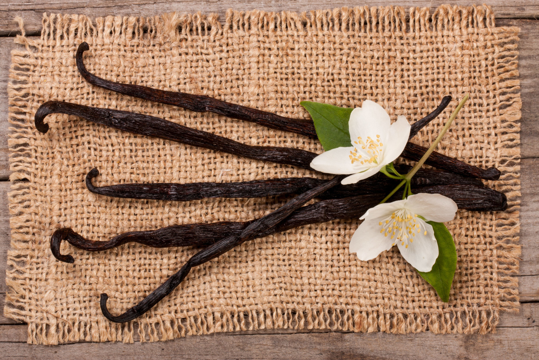 Vanilla sticks with flower and leaf on sackcloth.