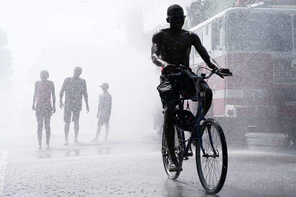 WASHINGTON, DC - JULY 04:  People cool themselves in water spray from a fire truck outside the annual Smithsonian Folklife Festival on Independence Day July 4, 2018 in Washington, DC.  An oppressive heat has settled over much of the nation and  is expected to last at least through the end of the week, according to forecasts.  (Photo by Alex Wong/Getty Images)
