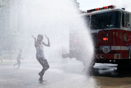WASHINGTON, DC - JULY 04:  Children cool themselves in water spray from a fire truck outside the annual Smithsonian Folklife Festival on Independence Day July 4, 2018 in Washington, DC.  An oppressive heat has settled over much of the nation and  is expected to last at least through the end of the week, according to forecasts.  (Photo by Alex Wong/Getty Images)