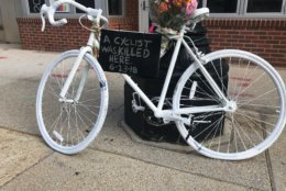 A so-called ghost bike painted white and decorated with a bouquet of flowers marks the spot where 19-year-old Malik Habib died. (WTOP/Dick Uliano)