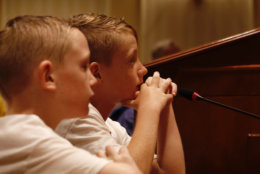 Andy Douglass, 10, and Charlie Douglass, 7, are the children of Jessica Douglass, who is running for state senate. They are seen listening to Sen. Will Smith discuss gun legislation at the post-rally meeting. (WTOP/Kate Ryan)