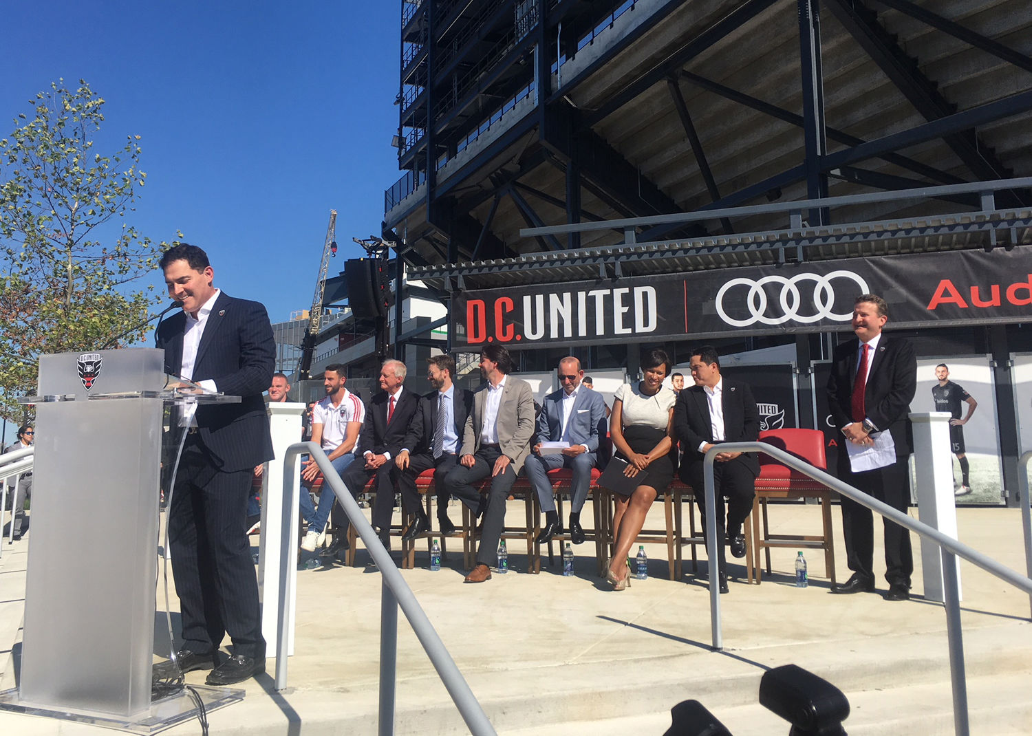 Jason Levien speaks in front of Audi Field's northwest gate as D.C. players, sponsors, politicians and MLS leadership look on. (WTOP/Noah Frank)