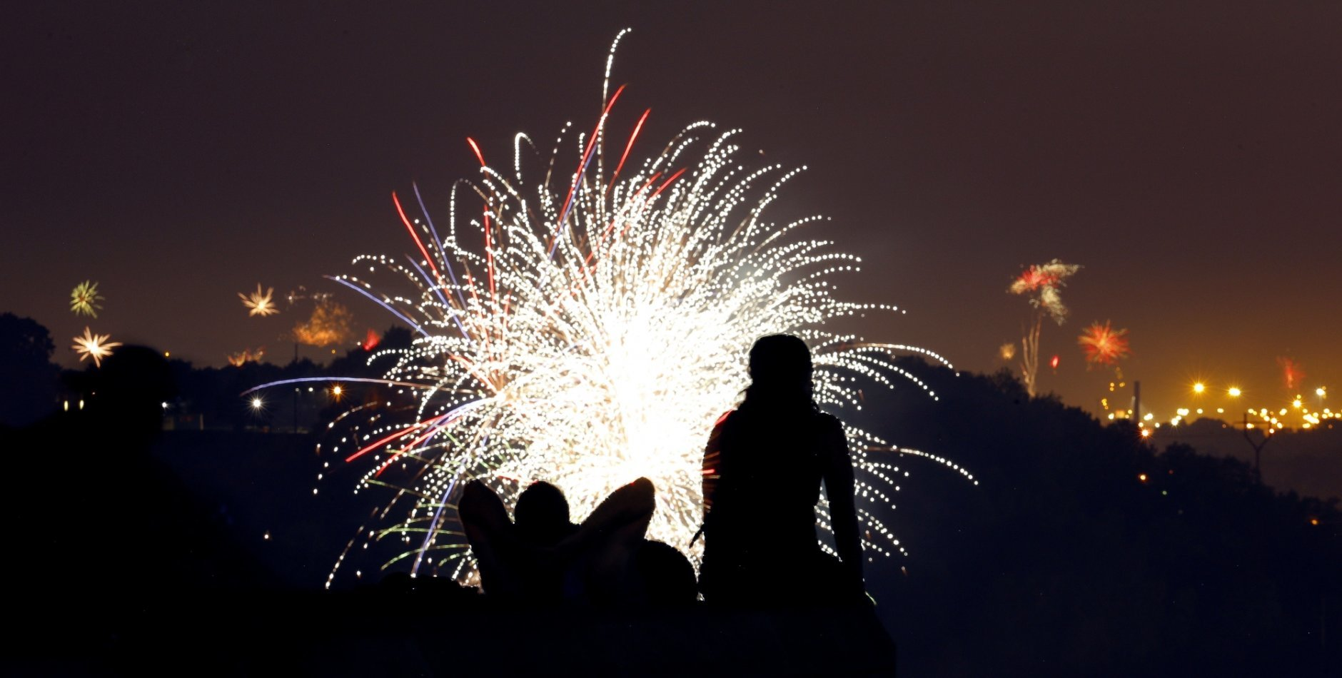 A couple watches fireworks set off by private citizens to celebrate Independence Day, from a vantage point at the Liberty Memorial on Wednesday, July 4, 2018, in Kansas City, Mo. (AP Photo/Charlie Riedel)