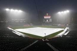 A tarp covers the infield during a rain delay in a baseball game between the Boston Red Sox and the Baltimore Orioles, Wednesday, July 25, 2018, in Baltimore. (AP Photo/Patrick Semansky)