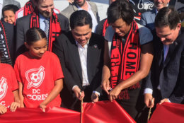 D.C. Mayor Muriel Bowser (second from right) cuts the ribbon at Audi Field with D.C. United General Partner Erick Thohir (left) and CEO and Managing General Partner and CEO Jason Levien (right). (WTOP/Noah Frank)