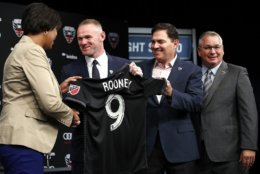 District of Columbia Mayor Muriel Bowser, left, shakes hands with English soccer star Wayne Rooney, the all-time leading scorer for England's national team and Manchester United in the Premier League, as he holds up his new jersey next to MLS team D.C. United Managing Partner and CEO Jason Levien, and Dave Kasper, General Manager and Vice President of Soccer Operations, right, during a news conference announcing Rooney's signing with D.C. United, Monday, July 2, 2018, at the Newseum in Washington. (AP Photo/Jacquelyn Martin)