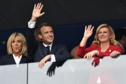 French President Emmanuel Macron, his wife Brigitte, left, and Croatian President Kolinda Grabar-Kitarovic wave prior to the final match between France and Croatia at the 2018 soccer World Cup in the Luzhniki Stadium in Moscow, Russia, Sunday, July 15, 2018. (AP Photo/Martin Meissner)