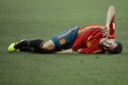 Spain's Nacho lies on the pitch after being tackled during the round of 16 match between Spain and Russia at the 2018 soccer World Cup at the Luzhniki Stadium in Moscow, Russia, Sunday, July 1, 2018. (AP Photo/Alexander Zemlianichenko)