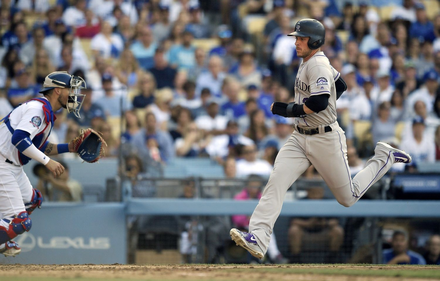 Colorado Rockies' Trevor Story, right, scores on single by Chris Iannetta as Los Angeles Dodgers catcher Yasmani Grandal looks for a throw during the seventh inning of a baseball game Saturday, June 30, 2018, in Los Angeles. (AP Photo/Mark J. Terrill)
