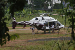 A helicopter waits near the cave for more evacuations of the boys and their soccer coach who have been trapped since June 23, in Mae Sai, Chiang Rai province, northern Thailand Monday, July 9, 2018. Thailand's interior minister says the same divers who took part in Sunday's rescue of four boys trapped in a flooded cave will also conduct the next operation as they know the cave conditions and what to do. (AP Photo/Sakchai Lalit)