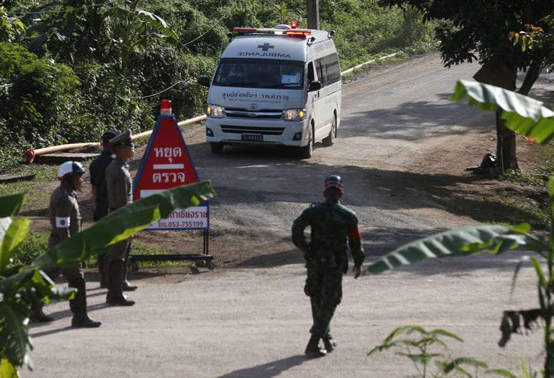 An ambulance with flashing lights leaves the cave rescue area in Mae Sai, Chiang Rai province, northern Thailand, Monday, July 9, 2018. The ambulance has left the cave complex area hours after the start of the second phase of an operation to rescue a youth soccer team trapped inside the cave for more than two weeks. (AP Photo/Sakchai Lalit)