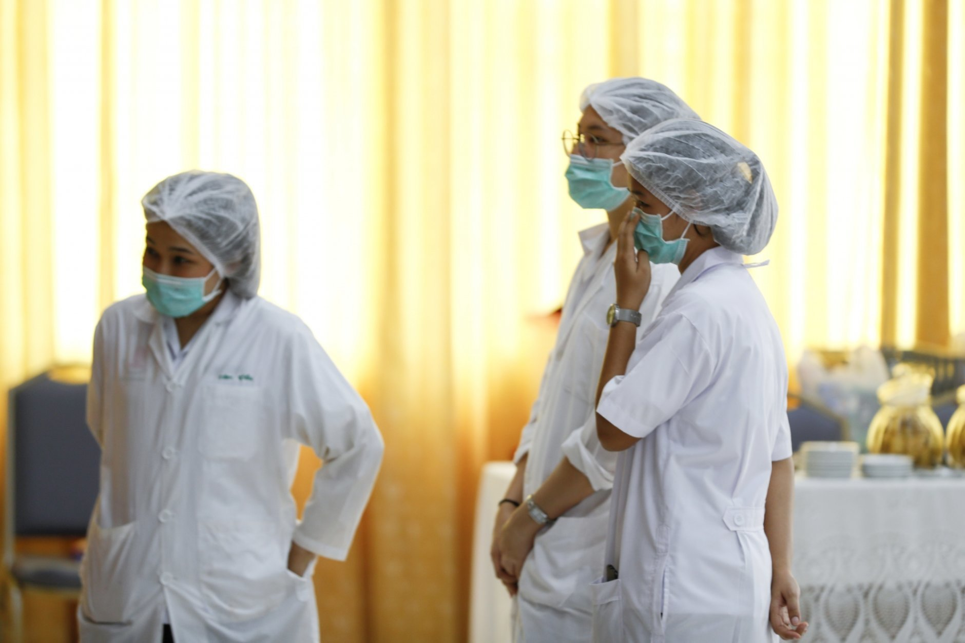 "Hospital workers watch a press conference at their hospital where rescued boys are tended to, in Chiang Rai province, northern Thailand, Tuesday, July 10, 2018. A Thai public health official said Tuesday the eight boys rescued from a flooded cave in northern Thailand are in ""high spirits"" and have strong immune systems because they are soccer players. (AP Photo/Vincent Thian)"